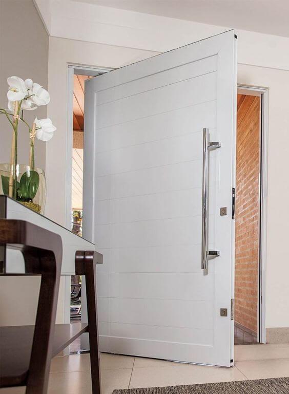Porta branca e grande na entrada de casa