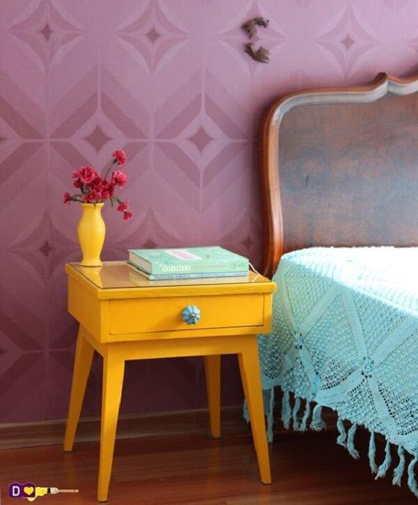 Quarto colorido com mesa de cabeceira retrô amarela, papel de parede roxo e colcha azul
