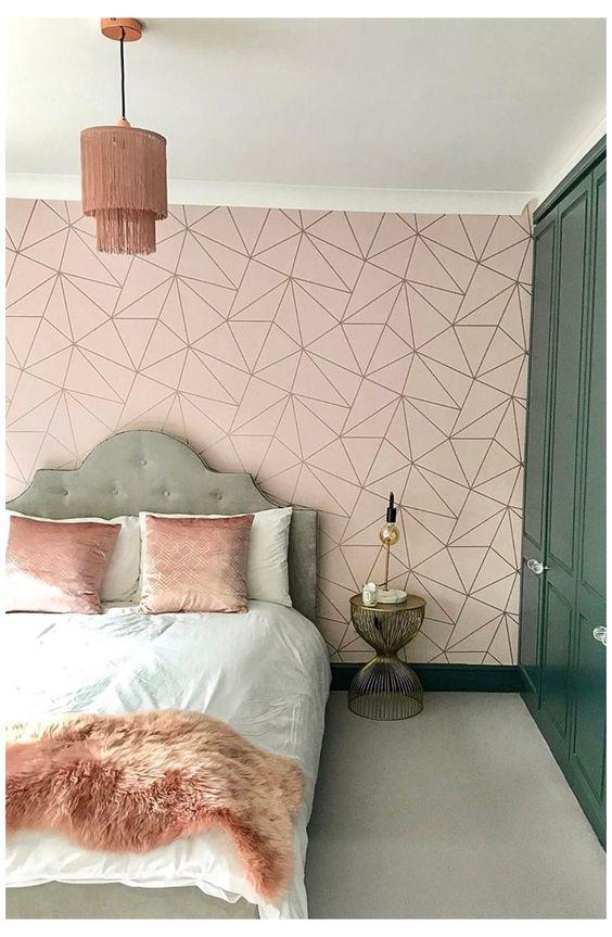 Quarto com papel de parede rosa e detalhes geometricos