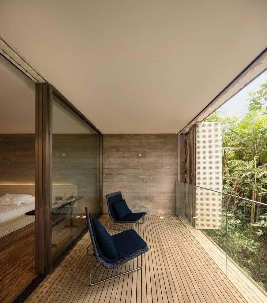 Quarto com varanda aberta separada por porta de vidro