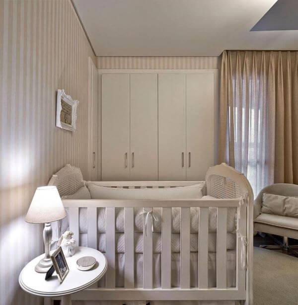 Quarto de bebê com papel de parede bege listrado