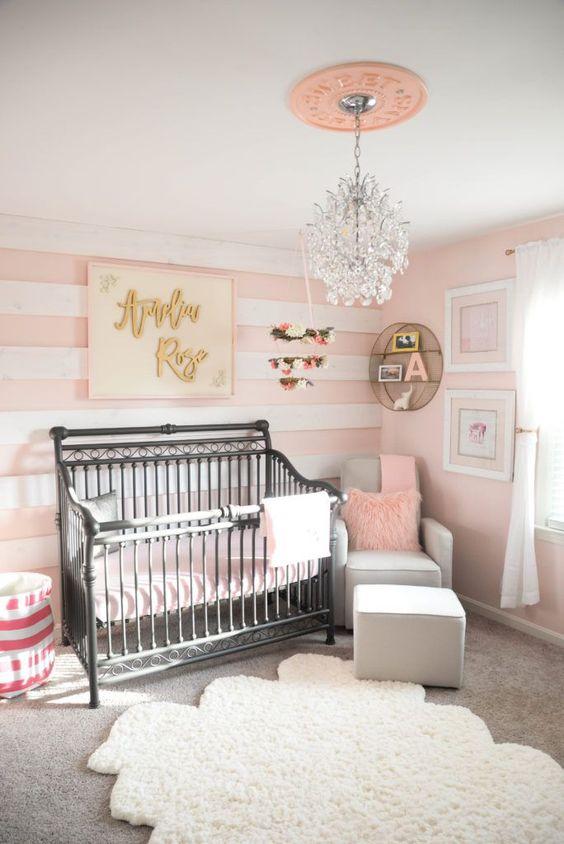 Quarto de bebe com papel de parede rosa listrado