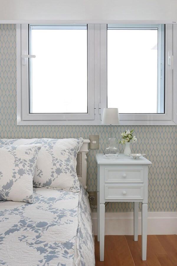 Quarto de solteiro com papel de parede geométrico e mesa de cabeceira retrô