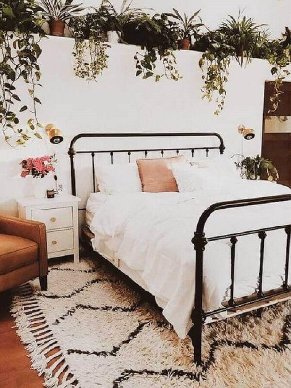 Quarto romântico decorado com vários vasos de plantas, cama de ferro e mesa de cabeceira retrô branca com gavetas