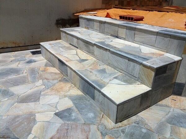 Revestimento de pedra São Tomé mesclado cobre o piso e os degraus da área externa