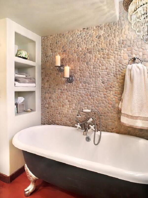 Revestimento de pedra bege em seixos decora a área da banheira