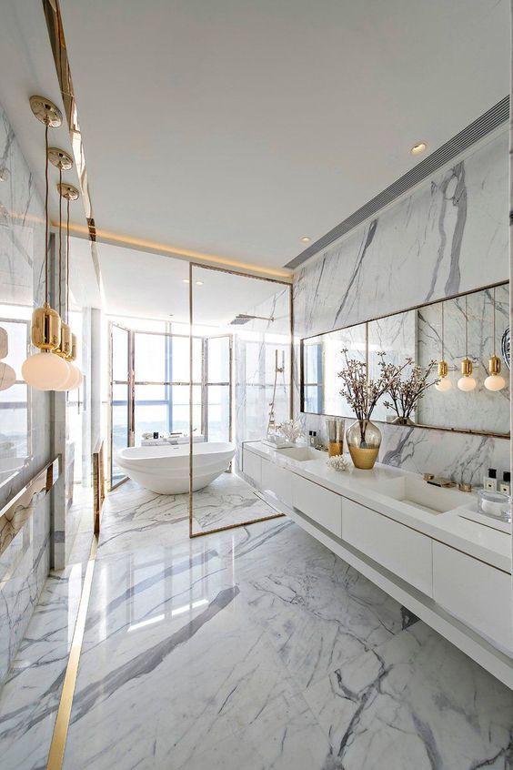 Revestimento marmorizado no banheiro amplo com detalhes dourados