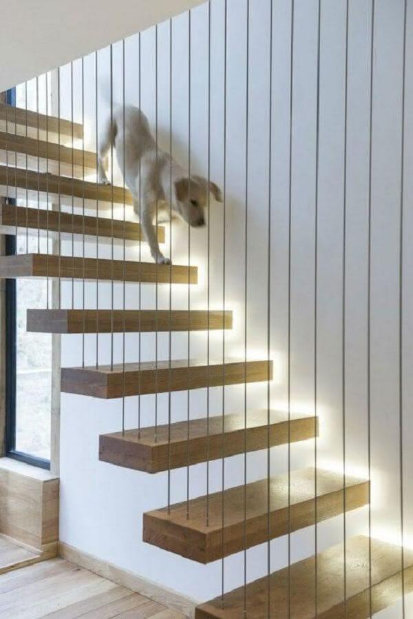 Revestimento para escada interna feita em madeira com guarda corpo feito em fios metálicos