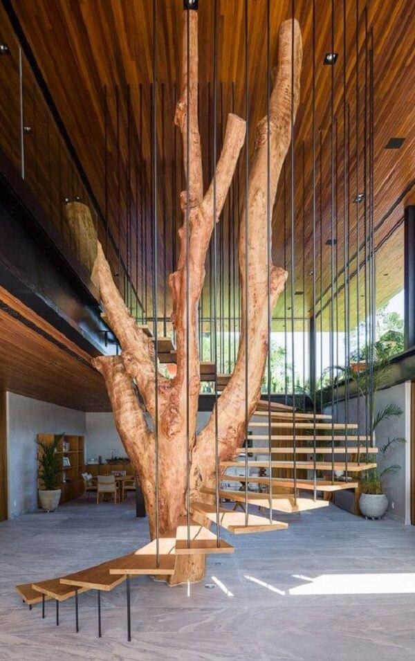 Revestimento para escada interna feita em madeira foi construída ao redor da árvore da sala