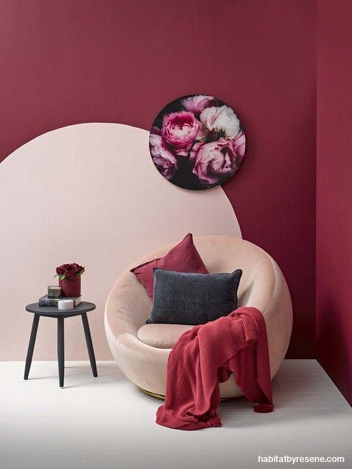 Sala aconchegante com puff bege e parede vinho