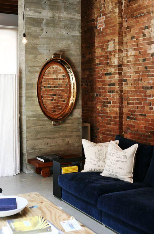 Sala com papel de parede rustico e sofá azul marinho