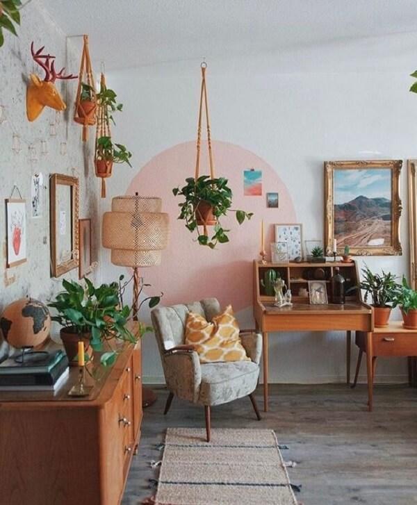 Sala com poltrona pé palito e decorada com inúmeras plantas