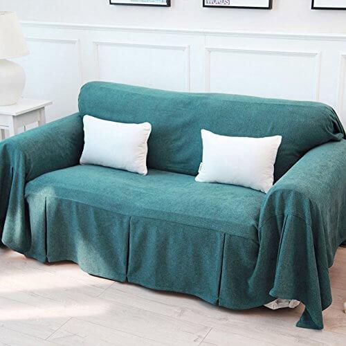 Sala com sofá coberto por tecido