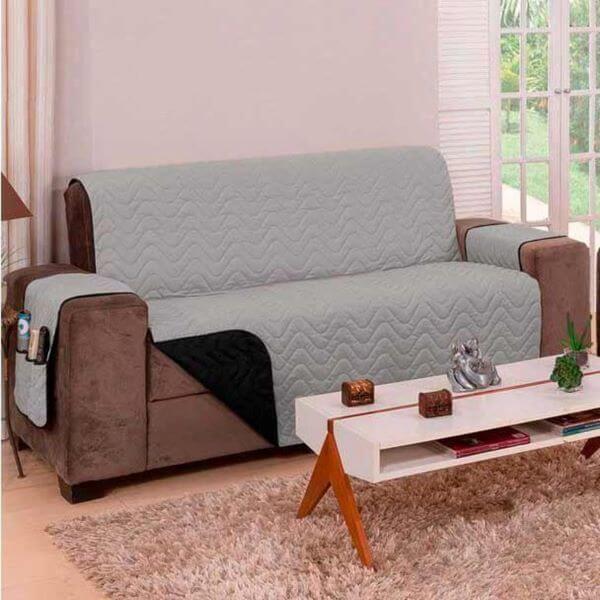 Sala com sofá marrom e capa impermeável cinza