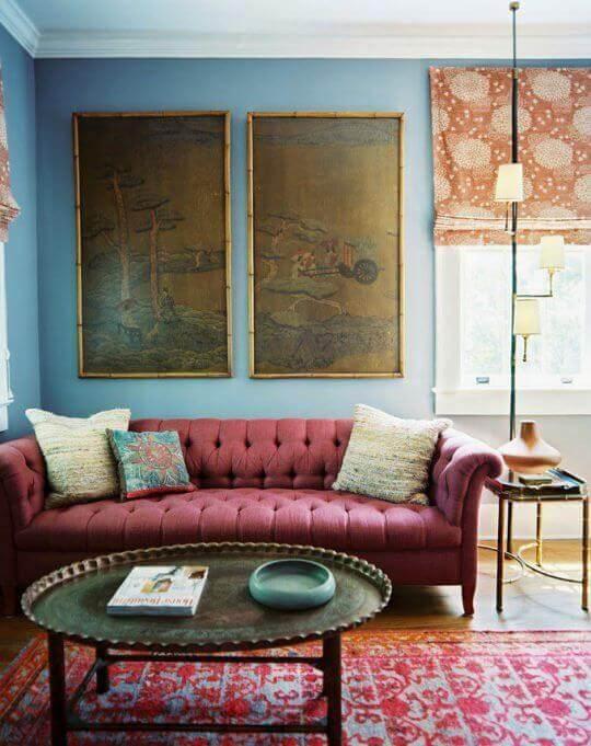 Sala com sofa na cor vinho e parede azul