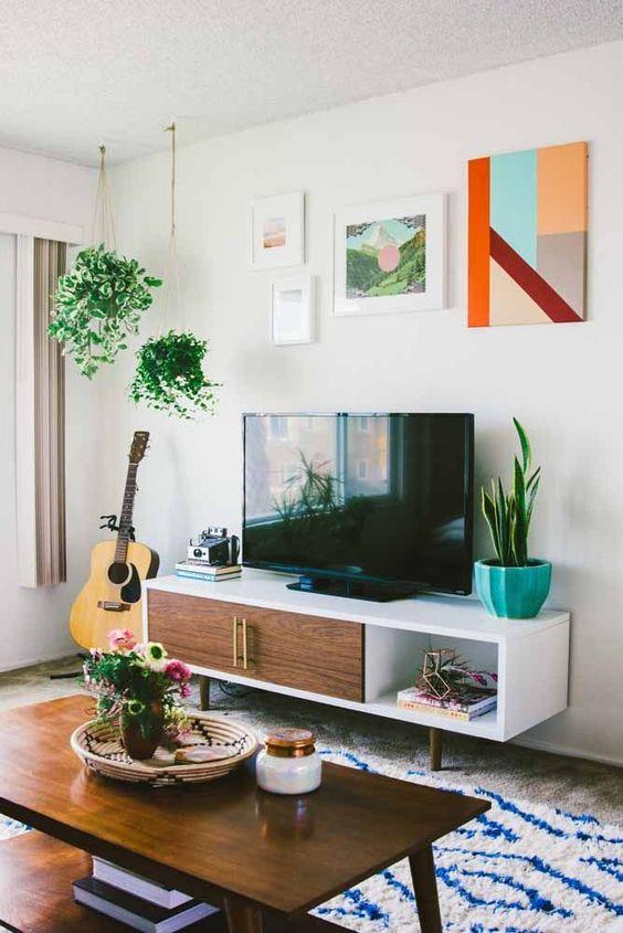Sala de estar com rack pe palito branco de madeira