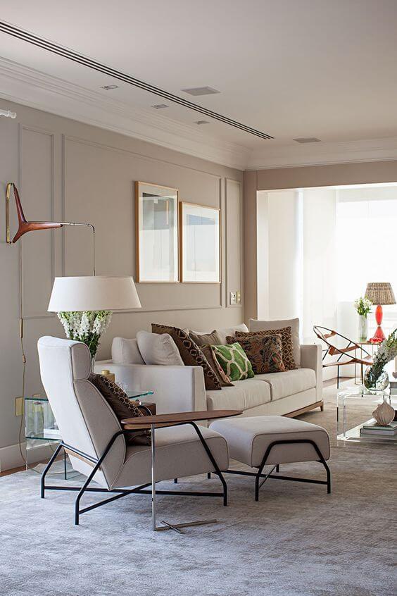 Sala de estar com revestimento bege e móveis claros