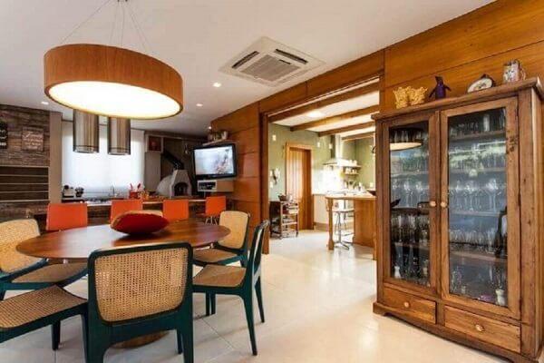 Sala de jantar decorada com mesa redondo e cristaleira de madeira rústica