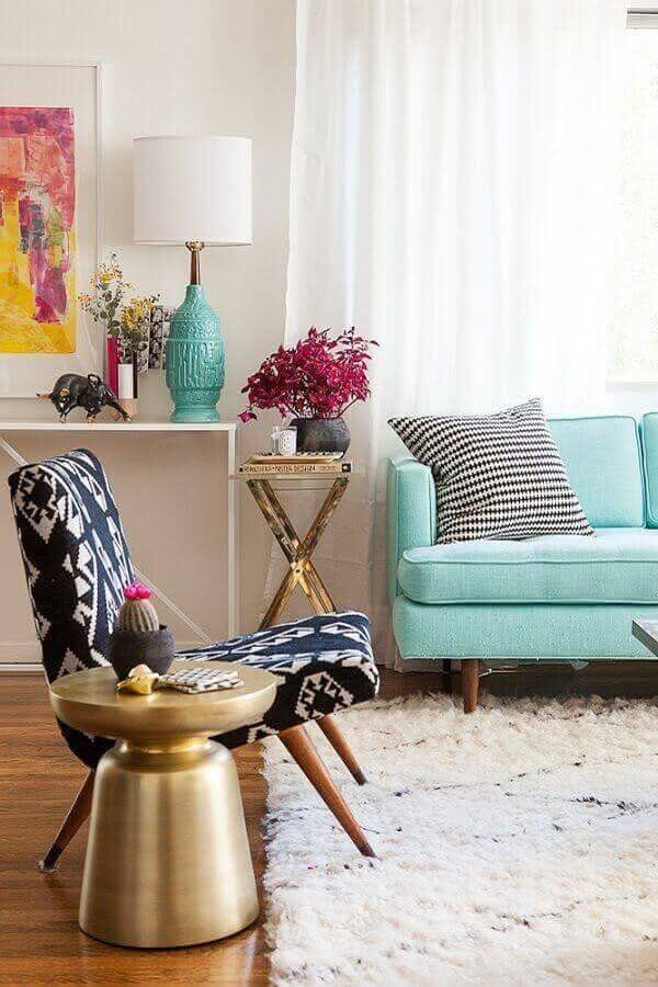 Sala decorada com tapete shaggy e poltrona pé palito preto e branca