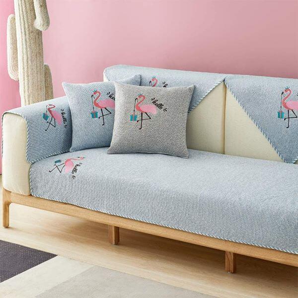 Sala rosa com capa de sofá azul claro e estampa de flamingo