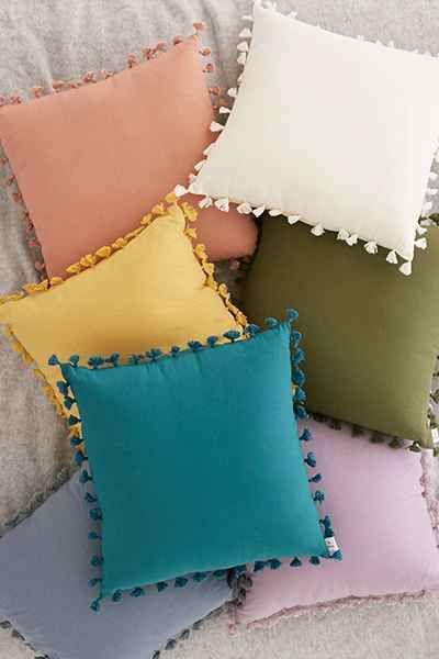 Tecido para almofada de diferentes cores no sofá cinza