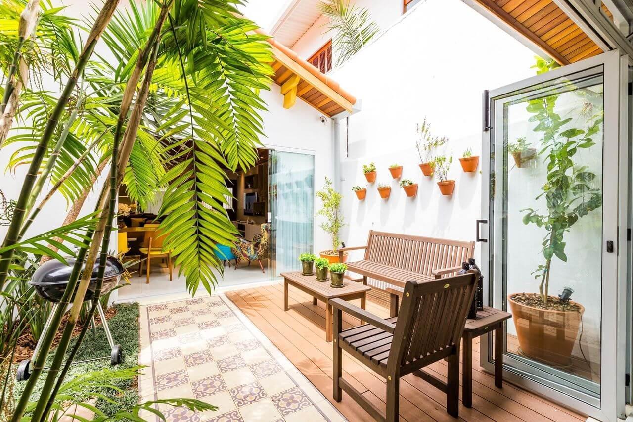 Terraço aberto decorado com piso de madeira e azulejo antigo