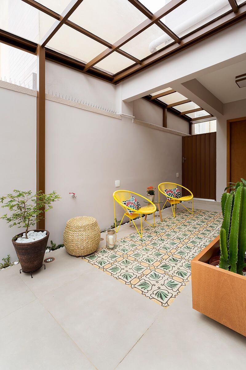 Terraço aconchegante com cadeira acapulco e piso de azulejo antigo colorido