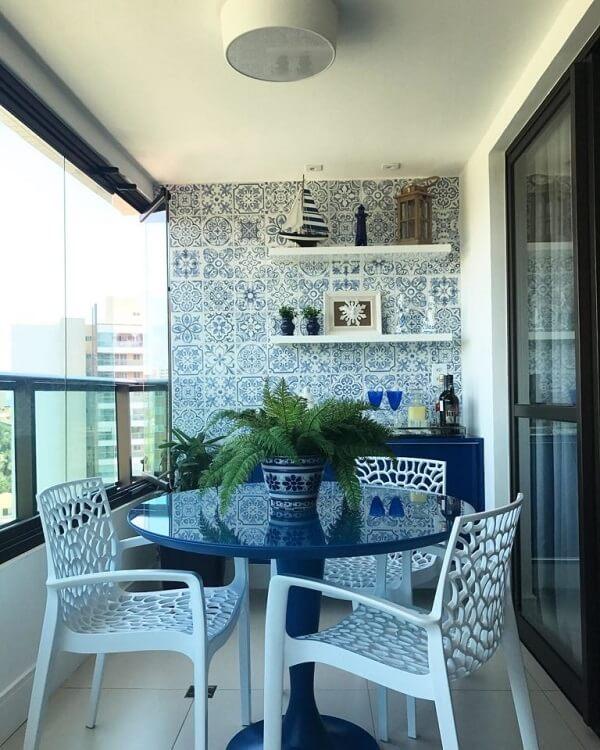 Varanda com móveis em tom de azul que se conectam com os azulejos antigos