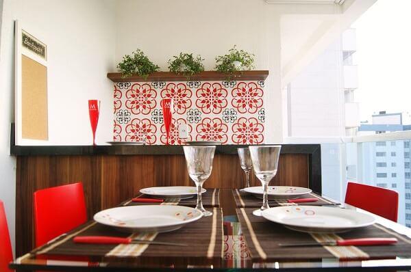 Varanda com parede de azulejos antigos com nuances em vermelho se conectam com as cadeiras da mesa