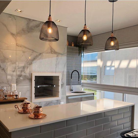Varanda gourmet com revestimento marmorizado na churrasqueira
