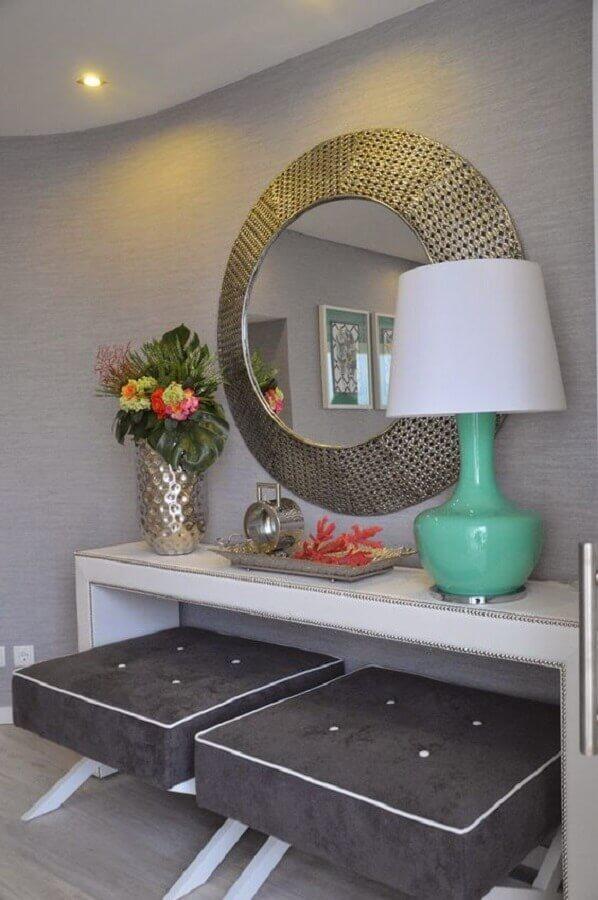 Aparador branco para sala cinza decorada com espelho redondo e abajur verde claro