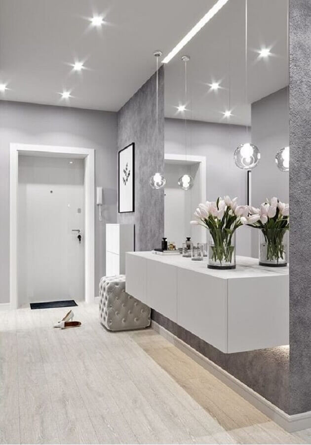 Aparador branco suspenso para corredor cinza decorado com parede espelhada