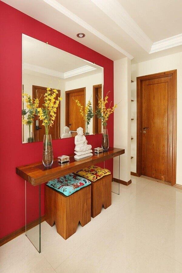 Aparador com espelho para hall de entrada decorado com parede vermelha
