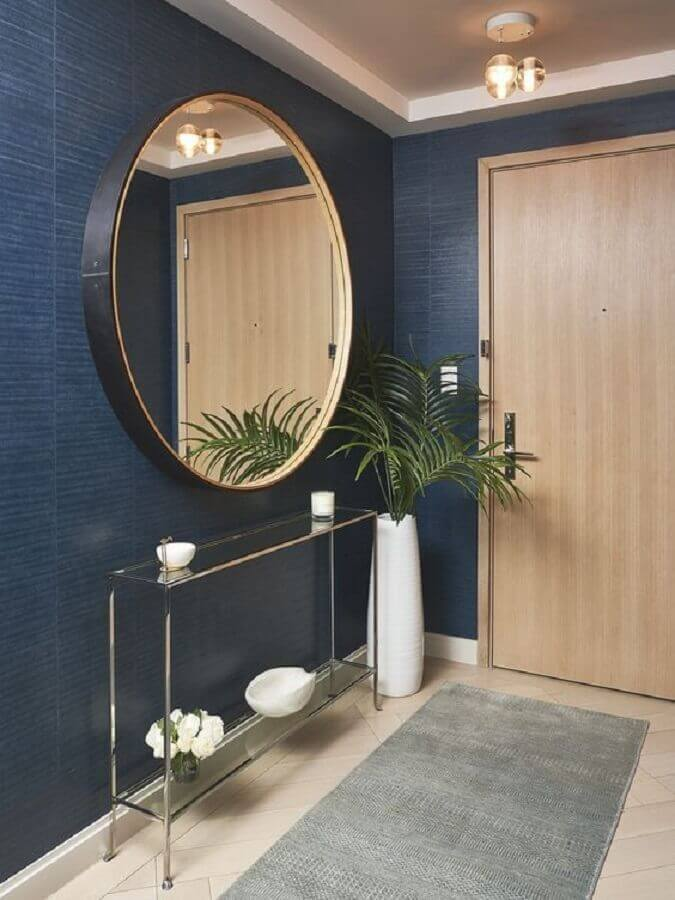 Aparador com espelho redondo para hall de entrada decorado com papel de parede azul escuro