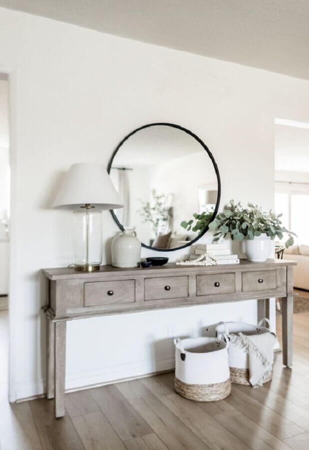 Aparador de madeira com gavetas e espelho redondo para decoração de corredor