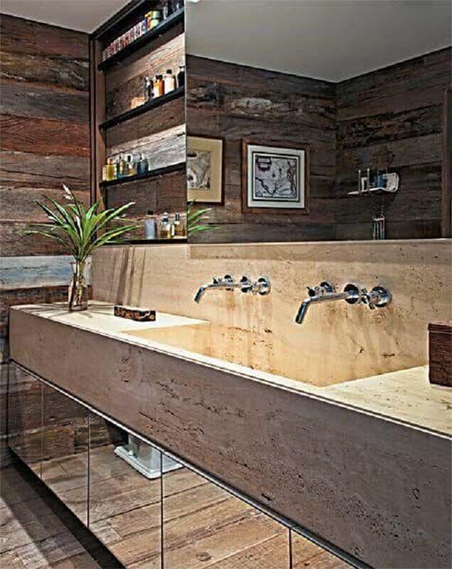 Banheiro decorado com bancada de mármore e parede com revestimento de madeira