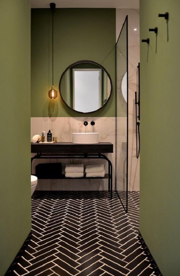 Banheiro moderno decorado com espelho redondo e parede cor verde oliva