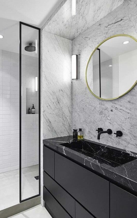 Banheiro sofisticado decorado com espelho redondo e bancada de mármore preto