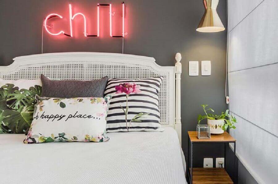 Cabeceira branca de madeira para quarto decorado com parede cinza e luminária neon