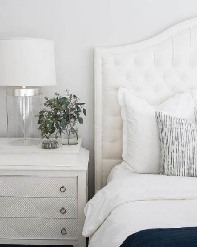 Cabeceira branca estofada para decoração de quarto clean com abajur de vidro