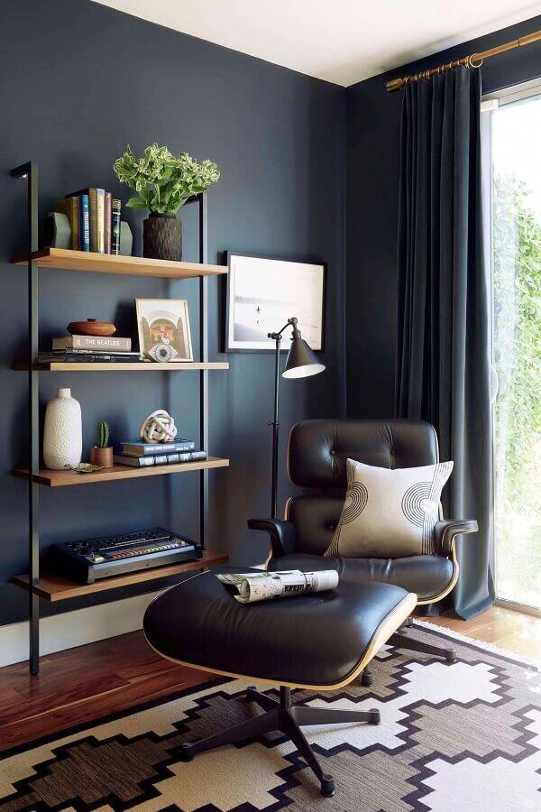 Cantinho de descanso decorado com poltrona preta de couro com puff