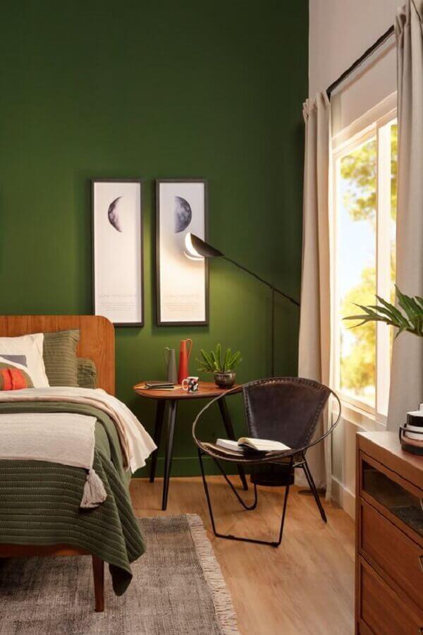 Cor verde para quarto de casal decorado com luminária de piso e cama de madeira