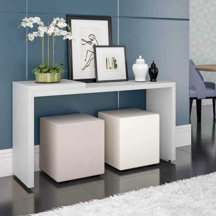 Corredor decorado com aparador simples branco e puffs quadrados