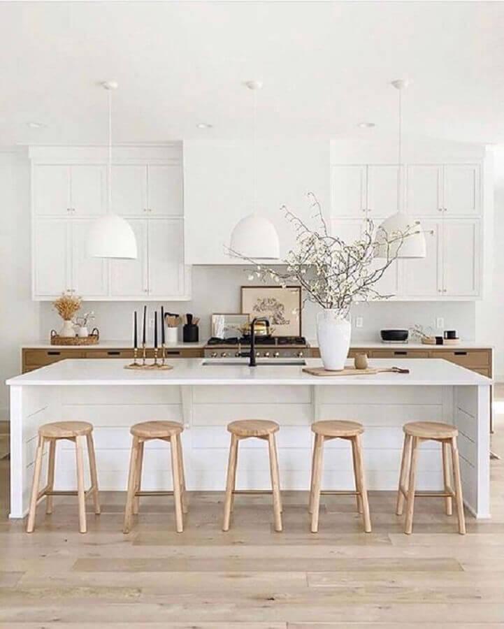 Cozinha branca com ilha decorada com banquetas para bancada de madeira