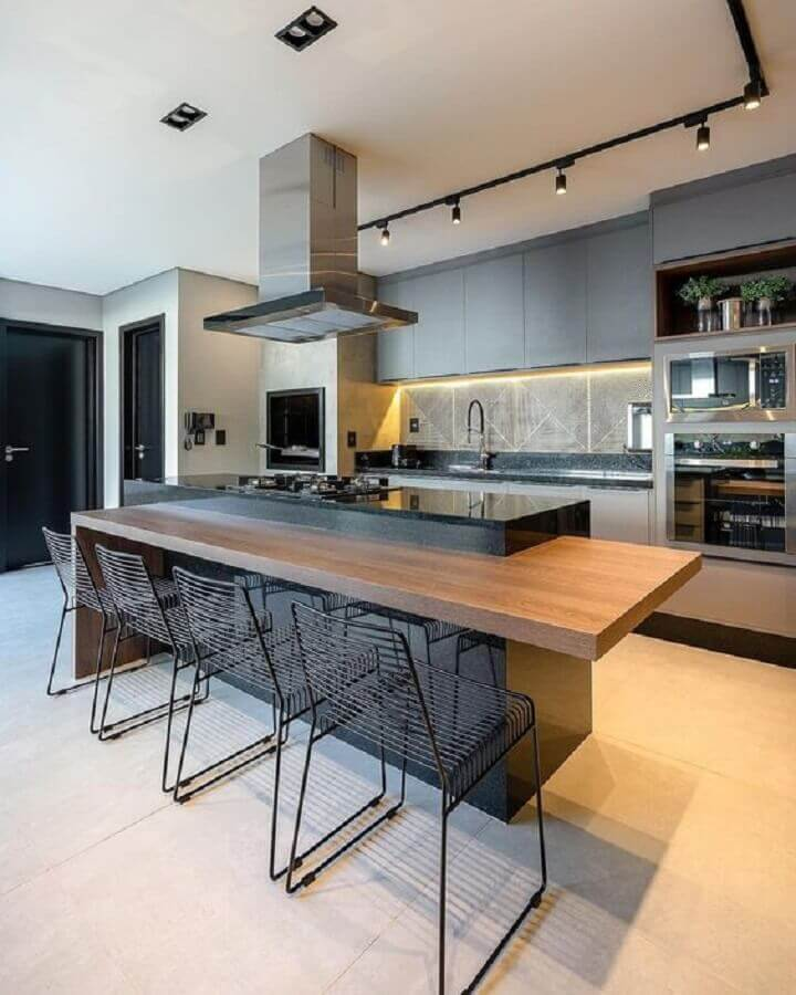 cozinha cinza moderna decorada com ilha gourmet com cooktop e bancada de madeira  Foto Decor Salteado