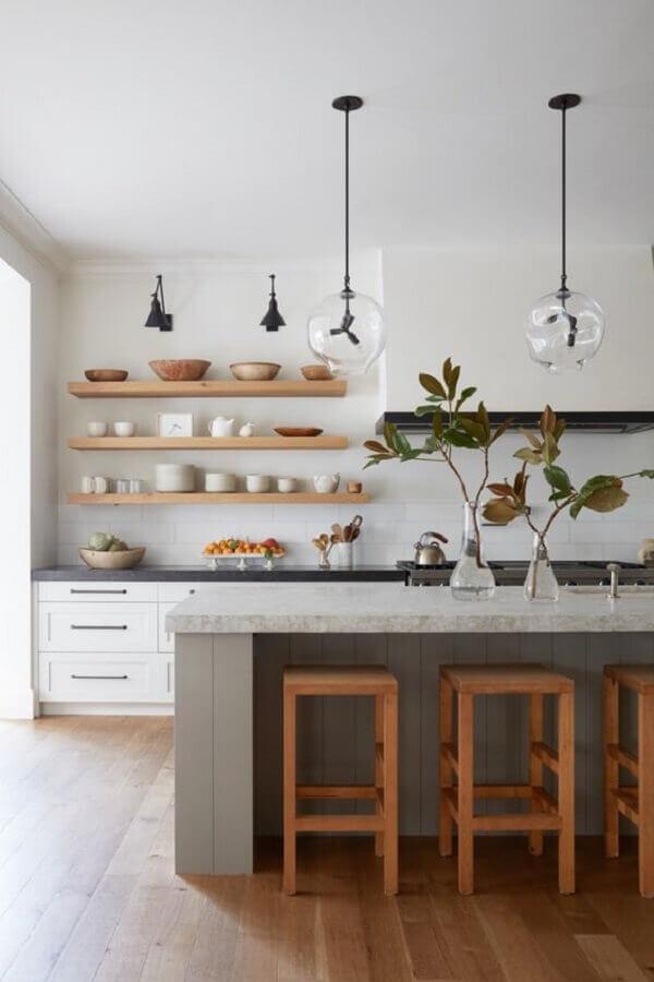 Cozinha com ilha decorada com banquetas de madeira para bancada