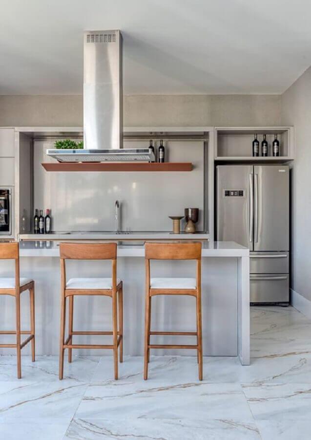 Cozinha com ilha decorada com banquetas para bancada de madeira