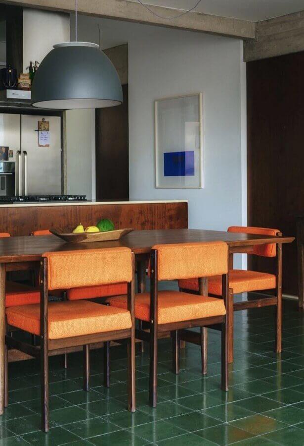 cozinha com ilha decorada com mesa de madeira e cadeiras acolchoadas  Foto História de Casa