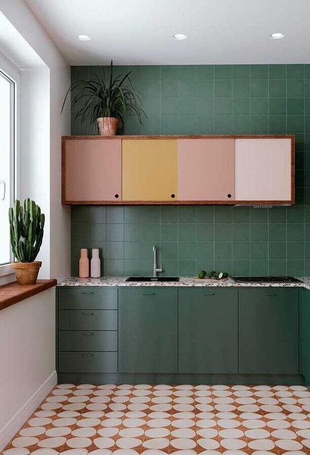 Cozinha cor verde escuro decorada com armário aéreo colorido