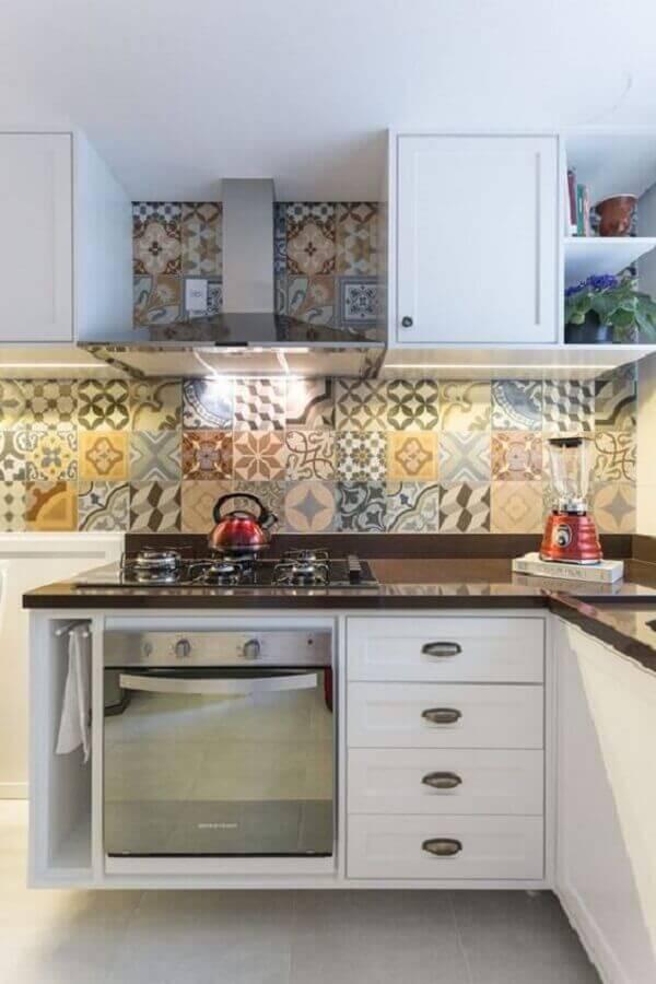 Cozinha planejada decorada com armários brancos e azulejo de cozinha colorido